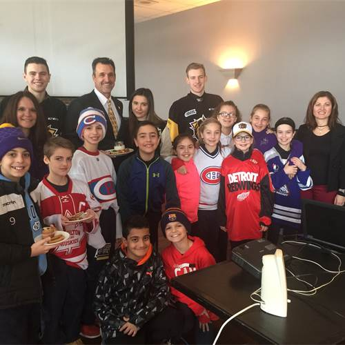 "Students from Corpus Christi join Owner and Chairman of the Hamilton Bulldogs Michael Andlauer (back row, second from left) and HWCDSB Assistant Superintendent Sandra Scime (far right) at the annual Bulldogs ""School Day"" game on Feb. 8th. The Hamilton Bulldogs Foundation supports school nutrition programs through its Dawgs Breakfast Program."